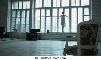 Sexy young woman dances opposite the window, lifting gracefully legs. A beautiful girl in a short white dress is dancing to the accompaniment of a man at the piano. Elegant dance with your feet.