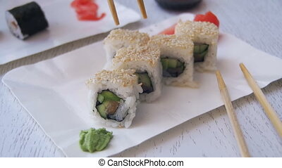 Chopsticks Taking Sushi Roll from a Plate and Dips into Soy...