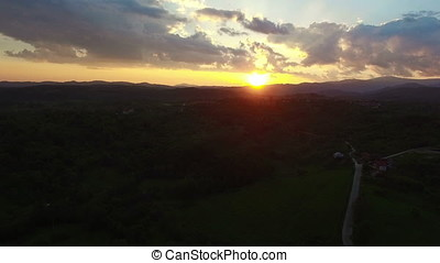 Flight over green hills and village against sunset