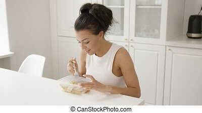 Young girl eating from container - Young female in home...