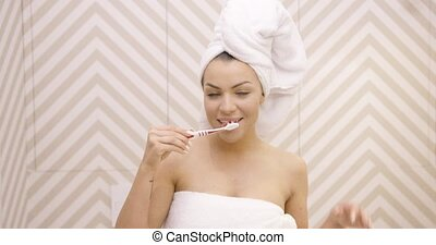 Smiling woman brushing teeth - Young beautiful female with...