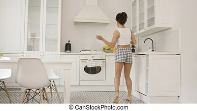 Female dancing in kitchen - Back view of young female...