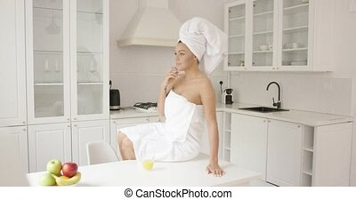 Female wrapped in towel sitting on table - Young fit woman...