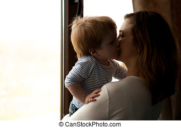 Mother kissing her baby boy son. Happy childhood and...