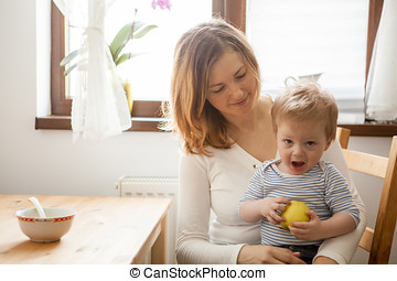 Baby boy in hands of her mother eating an apple