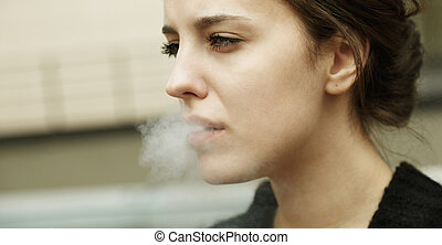 smoking kills - real young woman smokes on the street,...