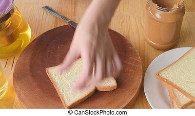 Woman making yummy peanut butter sandwich. - Spreading...