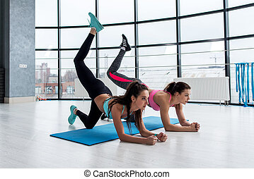 Slim young women doing bent knee donkey kick exercise in all...