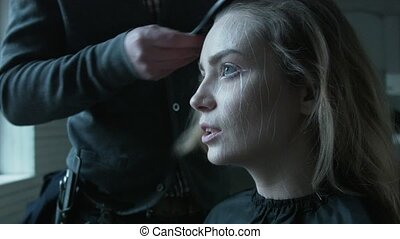 A professional stylist is preparing a beautiful model for a blonde to enter the podium. Professional hairdresser man combs hair to a young woman. Before shooting commercials.