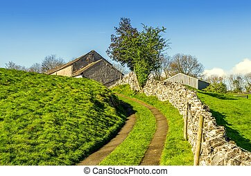 Winding lane leading uphill to a barn