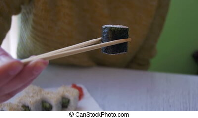 Woman Eating Sushi Roll with Nori from a Plate in a Japanese...