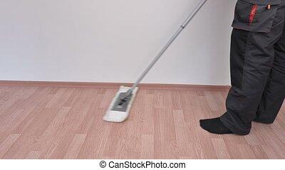 Worker using brush on floor