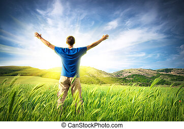 Happy freedom - Man in green meadow and sunshine. Conceptual...