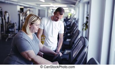 Overweight woman in gym with coach walking on treadmill. -...