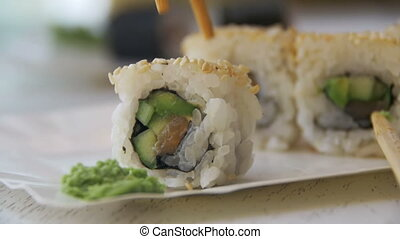 Chopsticks Taking Sushi Roll from a Plate in a Japanese...