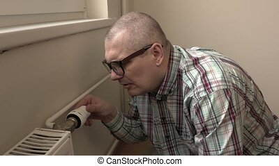 Man try adjusting radiator thermostat