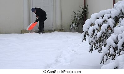 Man shoveling snow at footpath near house door entrance....