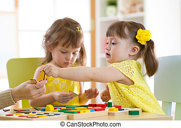 Preschool teacher and children playing with educational sorter toys in classroom
