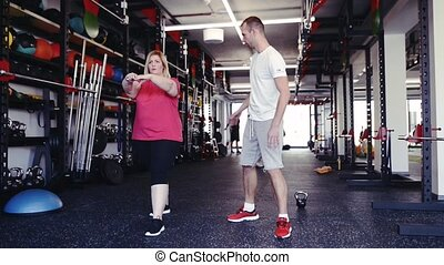 Overweight woman with personal trainer in modern gym. -...