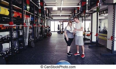 Fitness trainer with tablet in gym talking to new client. -...