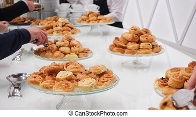 People take buns with raisins on a coffee break at a...