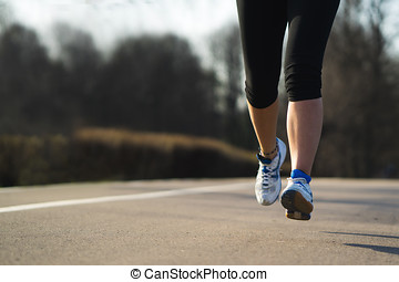 Fitness woman training and jogging in spring park, feet...