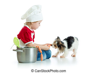 Role-playing game. Kid boy plays chef with dog. Child weared cook feeds hungry puppy.