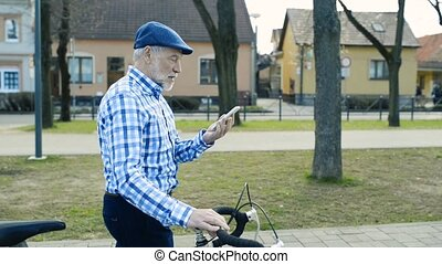 Senior man with smartphone and bicycle in town. - Handsome...