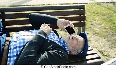Senior man with mart phone lying on bench, making phone call...