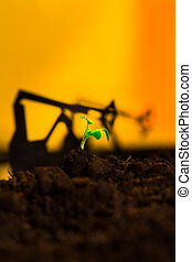 Young green plant in soil on background oil rocking machine