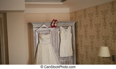 The bride's dress hangs on the hanger on the closet and the red