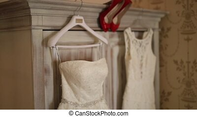 The bride's dress hangs on the hanger on the closet and the...