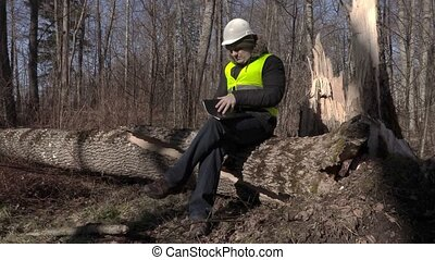 Lumberjack sitting and reading documentation on fallen tree in park