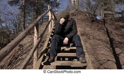 Depressed man sitting on wooden stairs