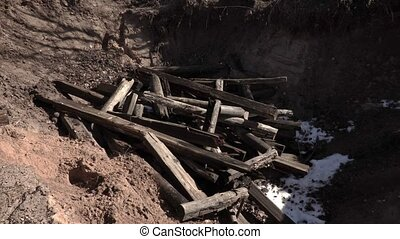 Worker throw pieces of wood into the pit