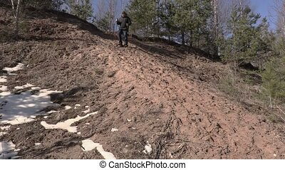 Man with hiking sticks stepping down from the hill