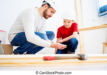 Father and son working together - Father and his son are...