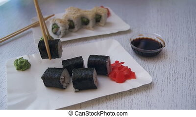 Chopsticks Taking Sushi Roll with Nori from a Plate in a Japanese Restaurant