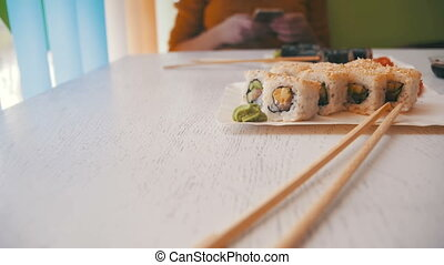 Woman in a Japanese Restaurant and Plates of Sushi Rolls on a White Stylish Wooden Table. Dolly Shot