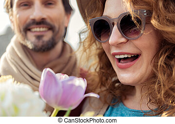 Cute lady getting flowers from man - Excited woman is...