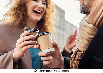 Cheerful man and woman drinking hot beverage