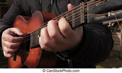 Man practicing to play the guitar in autum day