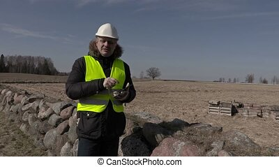 Building inspector using tablet near stone wall