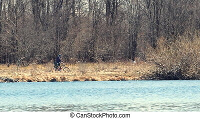 Man walks with a Bicycle on the river Bank. Along the river...