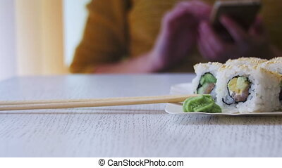 Plates of Sushi Rolls in a Japanese Restaurant on a White...