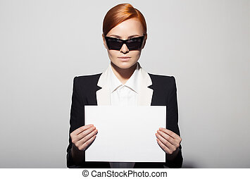 Fashion portrait of serious woman dressed as a secret agent or spy. Holding empty blank in hand.