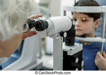 Old female oculist verifying vision of child