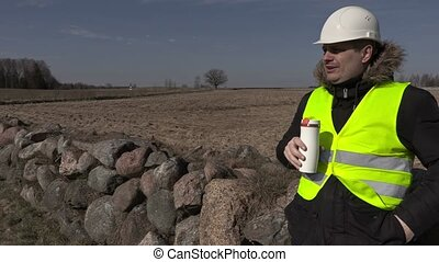 Building inspector drinking coffee near stone fence