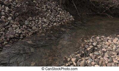 Man with hiking sticks across brook