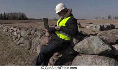 Building inspector sitting on stone fence and using laptop